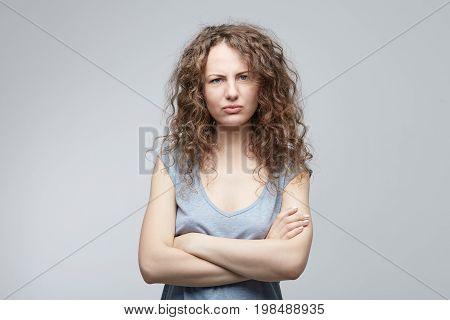 Indoor shot of angry attractive grumpy young female dressed casually keeping arms folded looking at camera with strict and skeptical expression of dissatisfaction. Insult teenager with placid look.