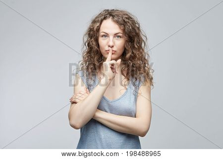 Shh!Attractive Caucasian curly haired lady looking the camera with big blue eyes holding index finger on lips asking to keep silence and not telling her secret. Secrecy privacy and confidentiality.