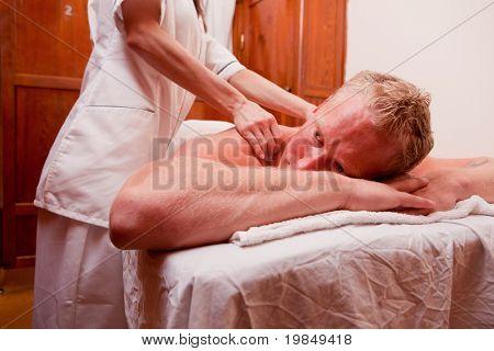 A man receiving a shoulder and back massage at a spa