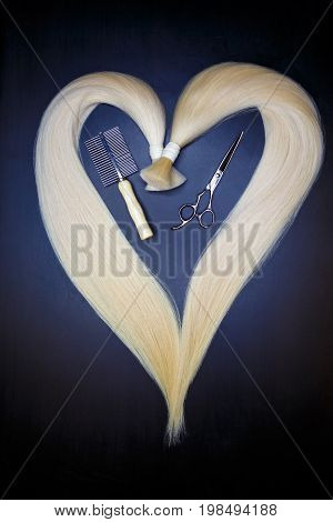 hair extension equipment of natural hair. heart shape on a dark background.