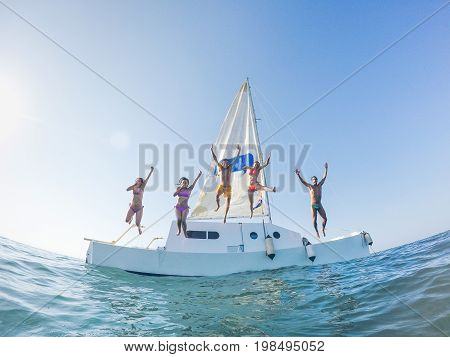 Happy friends jumping off the catamaran boat into the ocean - Young people having fun diving into the sea - Travel tropical summer and concept - Soft focus on center guys - Fisheye lens distorsion