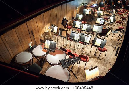 spectacle, dramatic art, music concept. in dark auditorium only orchestra pit is lightening, full of musical instrument, music stands and chairs trimmed with velvet for performers of accompaniment