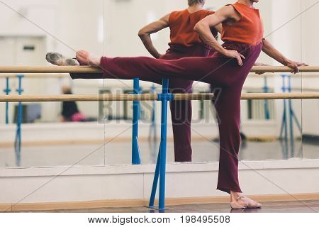dance, clothes, beauty concept. tough ballet dancer wearing cosy sweatpants in maroon colour and carrot-red sleeveless top doing exercises in dance hall nearby choreographic machine