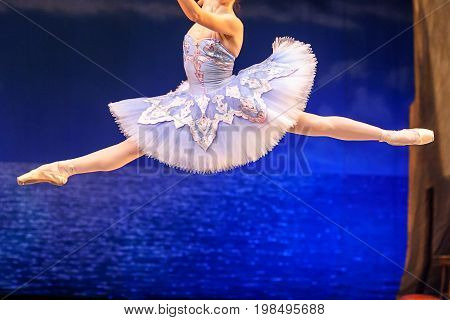 culture, ballet, clothes concept. ballerina, wearing magnificent blue costume with tutu, is in the air, in midflight, doing grand jete, high leap with stretched toes