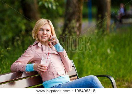 Girl with milkshake talking on phone sitting on bench at street in summer