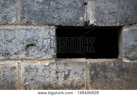 Rectangular black hole in a gray wall of concrete stones