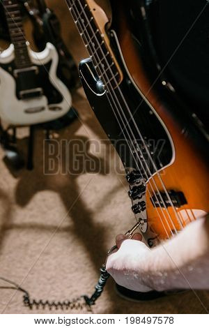 Guitarist connecting bass guitar in studio. Creative hobby for men, rehearsal process for band, music concept
