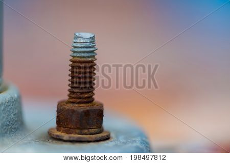 Old rusty steel bolt and nut with flat metal washer selective focus.