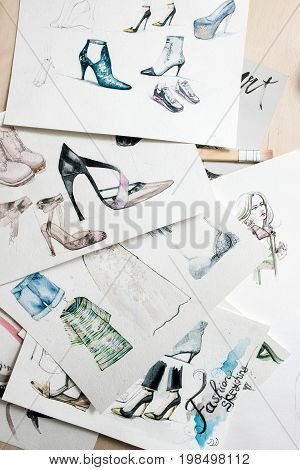 Patterns of fashion sketching models of footwear and clothing. Workplace of fashion designer