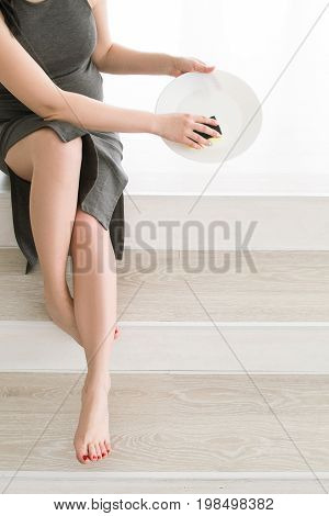 Young pregnant woman washes a plate at home. Housework routine, cleaning and household concept during mother-to-be period