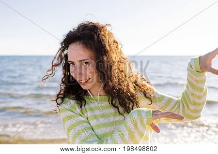 young woman have fun and listening to music on beach on background of sea. Curly girl dancing with earphones and phone outdoor