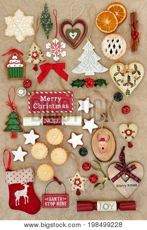 Symbols of christmas with bauble decorations, ornaments and signs on handmade hemp paper background.