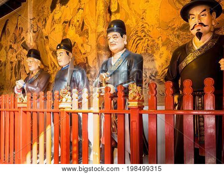 Shanghai, China - Nov 6, 2016: Inside the 600-year-old Old City God Temple. Statues of huge Taoist guards standing along the wall. Low-light image.