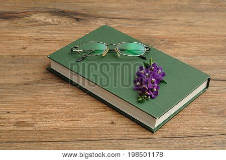 Small purple flowers with a hardcover storybook and spectacles