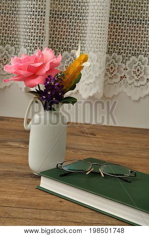 Colorful flowers in a vase with a hardcover storybook and spectacles