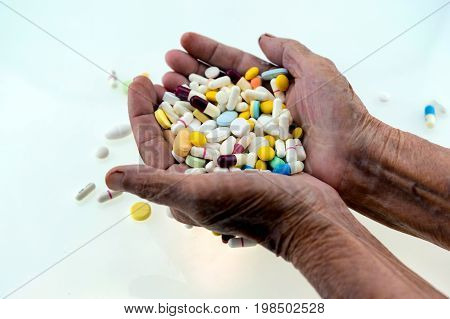 Many Multi-colored Pills In A Senior's Hands On White Background; Alzheimer's Patients; Caring For T