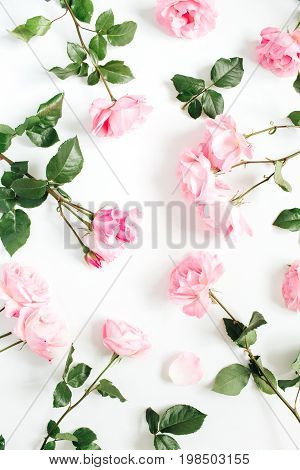 Floral pattern made of pink roses green leaves branches on white background. Flat lay top view. Valentine's background. Floral pattern. Pattern of flowers. Flowers pattern texture