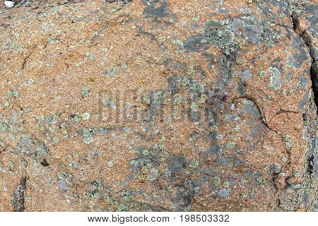 Granite rock with moss background. Background of stone surface. Textured processing hard stone. Decorative antique.