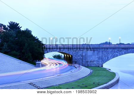 Long-exposure shot of traffic passing through short tunnel at dusk.