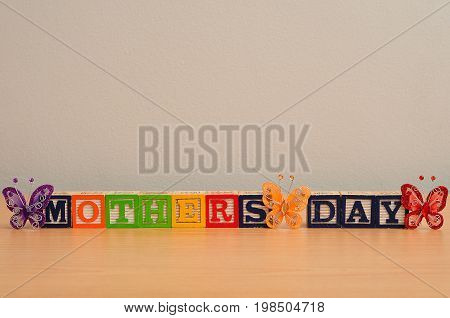 Mothers day with silk butterflies on a wooden background