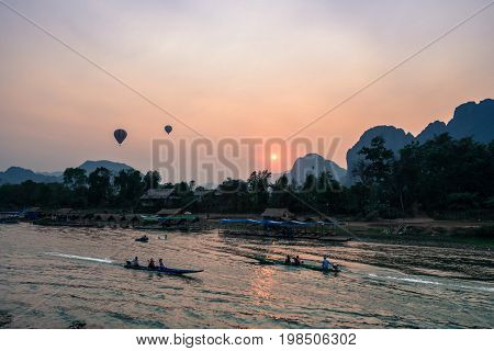 Horizontal picture of sunset over Nam Song River with two hot air ballons and tourists on the boat in Vang Vieng Laos.