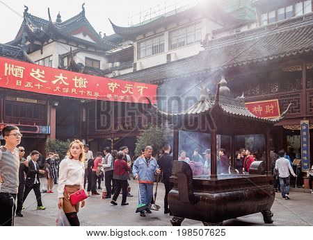 Shanghai, China - Nov 6, 2016: Inside the 600-year-old Old City God Temple, near the Wealth God Hall. A large ornate bronze incense urn, intricately designed, with smoke rising upwards.