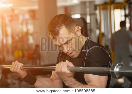 Handsome Young Man Training Biceps Lifting Barbell In A Gym With Sunlight