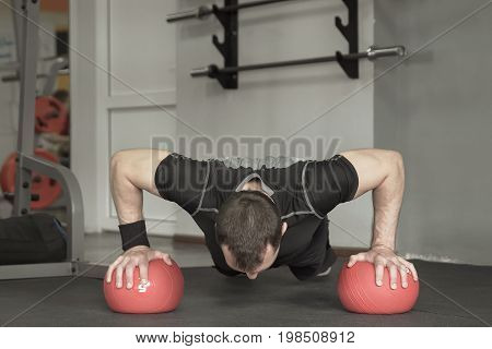 Sportsman Wearing Black Shorts And T-shirt Doing Push-ups Exercise On The Ball In Gym.