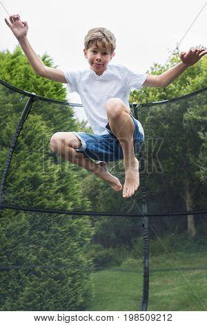 Mid Air Shot Of Boy On Trampoline In Garden