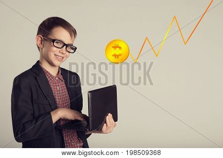 Young Smiling Business Child In A Suit And Eyeglasses Holding Laptop In His Hands. Young Man Looking