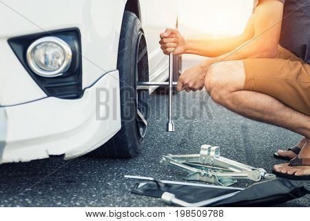 Asia man with a white car that broke down on the road.Changing tire on broken car on road.