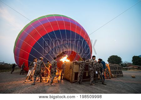 VANG VIENG LAOS - MARCH 15 2017: Local lao people using fire to heat the air inside the balloon before the sunrise in Vang Vieng Laos.