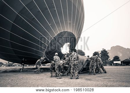 VANG VIENG LAOS - MARCH 15 2017: Black and white picture of people using fire to heat the air inside the balloon before the sunrise in Vang Vieng Laos.
