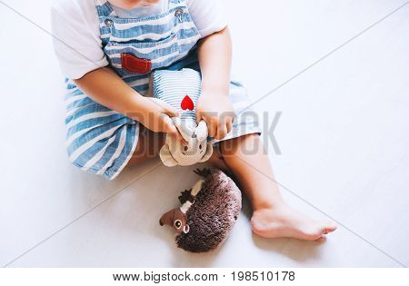 Сhild playing with soft toys at home on the floor. Cute little boy with teddy bear. Family concept background. Top view copy space.
