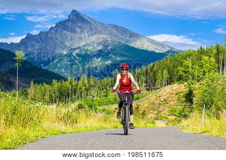 Happy woman on MTB bike on road in Ticha valley at High Tatras mountains Slovakia.
