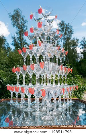 Pyramid of glasses of champagne at outdoor garden in wedding ceremony. outdoor bar open air