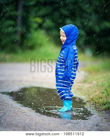 Child walking in wellies in puddle on rainy weather. Happy boy in raincoat