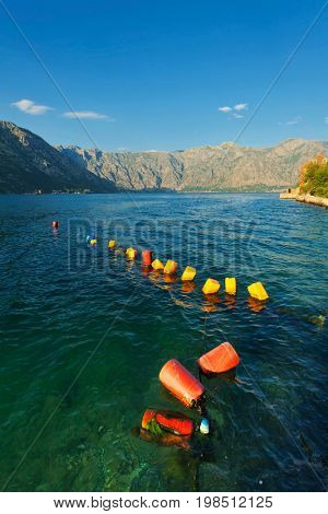 Row of red and yellow buoys in sea. Montenegro