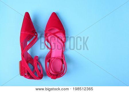 Stylish flat shoes on color background