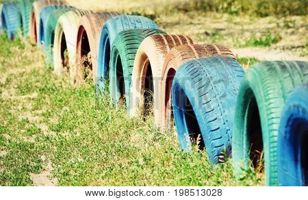 Fence made of old tires, outdoors. Waste recycling concept