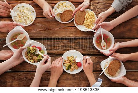 Hands of people eating at wooden table. Poverty concept