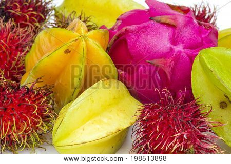 Tropical fruit colorful background group of starfruit dragonfruit and rambutan pink yellow red green on white isolated