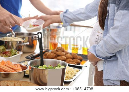 Pregnant woman receiving food from volunteer. Poverty concept