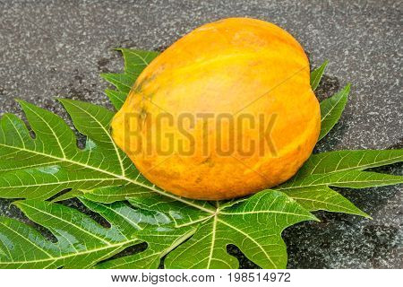 Fresh sweet papaya fruit and papaya leaf on a granite table. Raw food diet. Healthy lifestyle. Natural organic products. Selective focus.