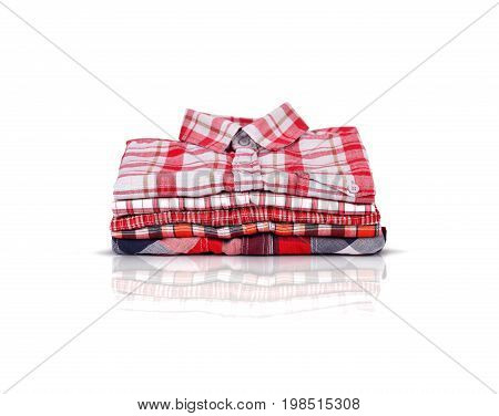 A stack of red shirts.White background on which lie folded red shirts.