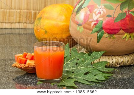 Fresh papaya juice in the glass with papaya fruits papaya leaf and slices on a granite table. Raw food diet. Healthy lifestyle. Natural organic products. Selective focus.