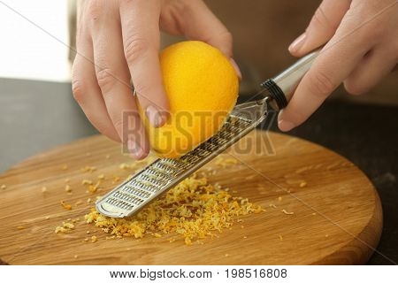 Woman grating zest of lemon on kitchen table