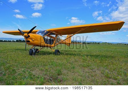Light sport yellow airplane stands on grass against a blue sky
