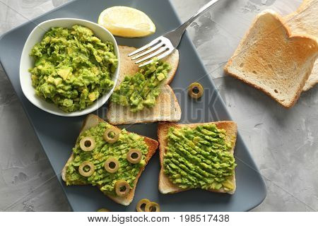 Bowl and delicious toasts with avocado and olives in platter on stone table