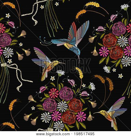 Embroidery humming bird and flowers seamless pattern. Beautiful hummingbirds and summer flowers embroidery on black background. Template for clothes textiles t-shirt design